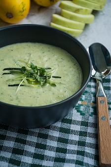 Courgettesoep gegarneerd met kruiden.
