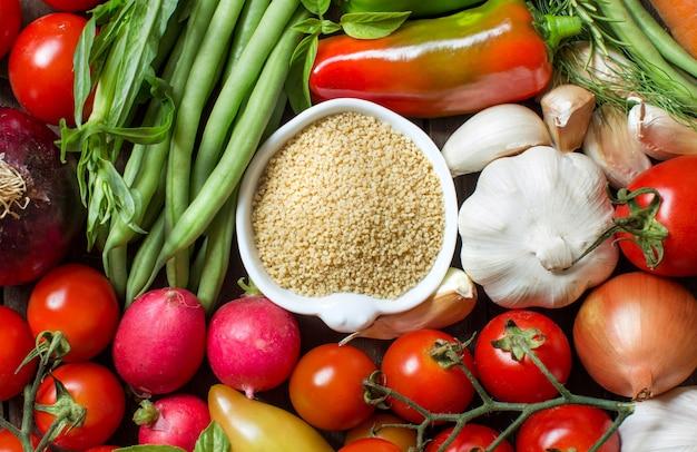 Couscous in een kom en verse groenten bovenaanzicht
