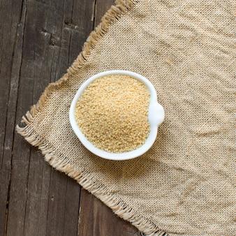 Couscous in een kom op jute bovenaanzicht op houten tafel