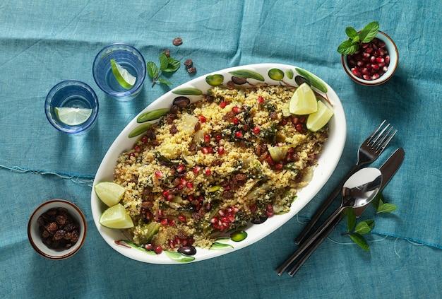 Couscous wordt gekookt op sinaasappelsap met gekookte groenten, gekarameliseerde uien, rozijnen en granaatappelpitjes. op de tafel met een linnen tafelkleed