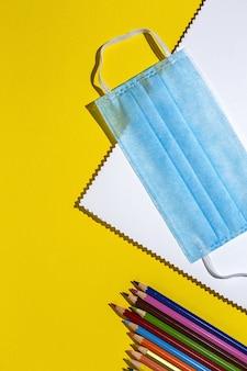Covid 15. nieuwe normaliteit. terug naar schoolbenodigdheden, notitieboekjes, kleurpotloden
