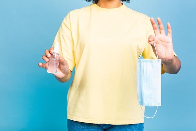 Covid-19 concept. afro-amerikaanse zwarte vrouw desinfecterende huid met handdesinfecterend middel geïsoleerd op blauwe achtergrond. coronavirus concept.