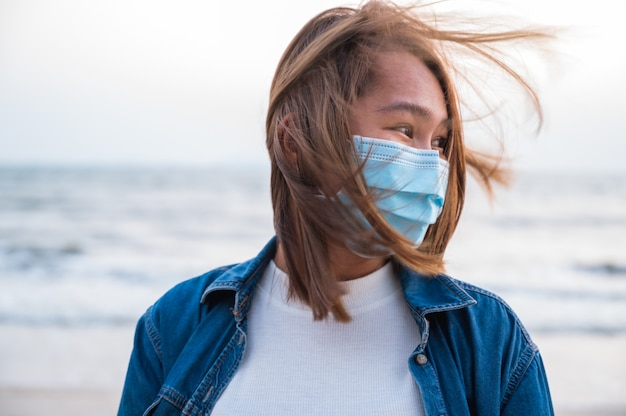 Covid-19 concept, aziatische jonge vrouw met een hygiënisch beschermend masker over haar gezicht buiten met zonsondergang op het strand