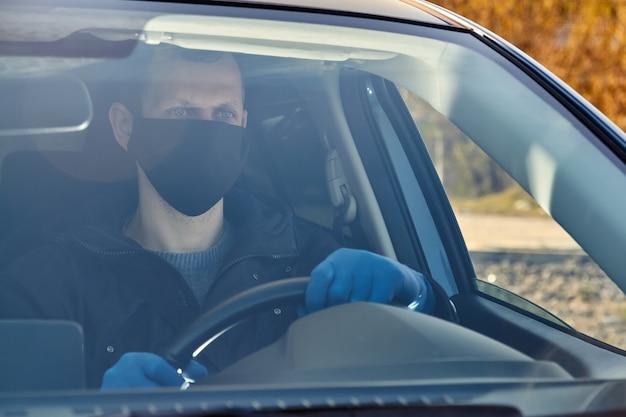 Covid-19 concept. man rijdt een auto in blauwe beschermende medische handschoenen en zwarte gezichtsmasker.