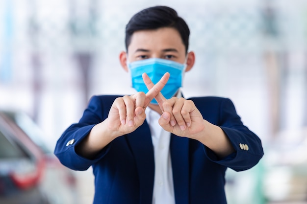 [covid-19] coronavirus concept.man met masker om pm2.5 te beschermen en handgebaar te tonen voor het stoppen van covid-19-uitbraak. wuhan coronavirus en epidemische virussymptomen.