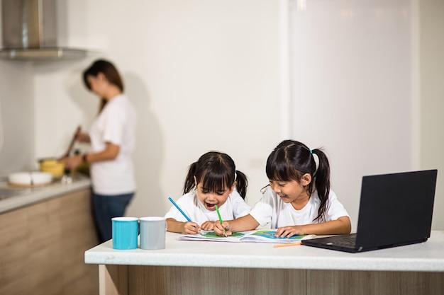 Covid-19 coronavirus en leren vanuit huis, thuisschoolconcept. kleine kinderen studeren online leren vanuit huis met laptop.