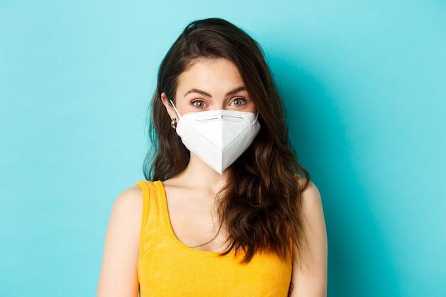 Covid-19, coronavirus en sociale afstand. aantrekkelijke jonge vrouw die een gasmasker draagt van het coronavirus, kijkend naar de camera, blauwe achtergrond