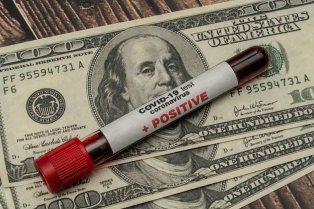 Covid 19 coronavirus, geïnfecteerd bloedmonster in de monsterbuis, op amerikaanse dollars, medicijnen