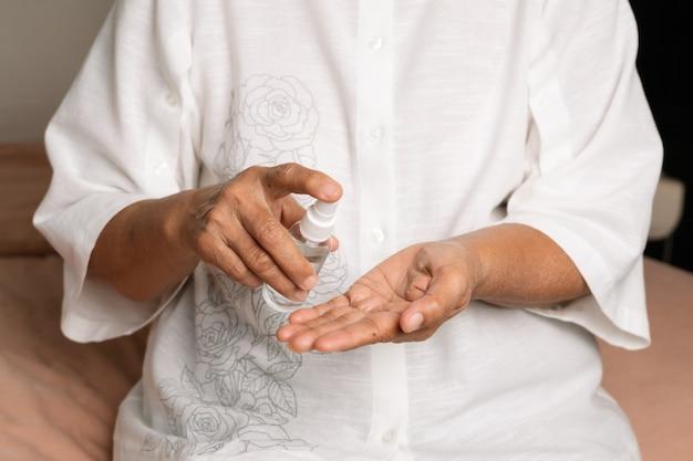Covid-19 coronavirus handreinigingsconcept, senior hand brengt alcoholgel of antibacteriële zeep aan om het virus, de kiem, de bacteriën te reinigen en te verwijderen