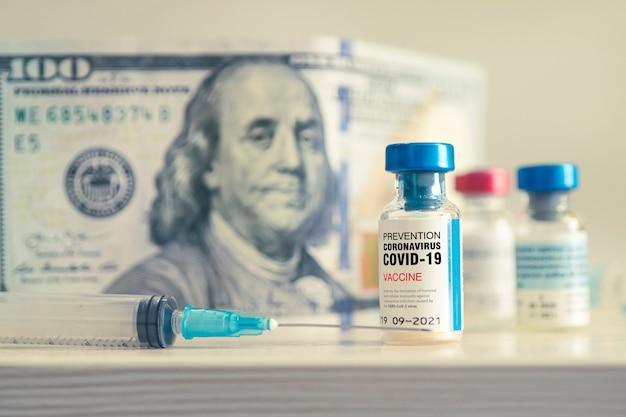 Covid-19 coronavirus infectie vaccin en een spuit op tafel tegen de achtergrond van geld. het concept van dure vaccinproductie.
