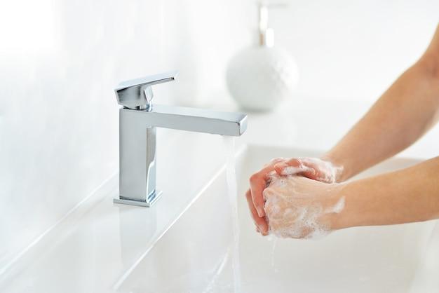 Covid-19 coronaviruspreventie handen wassen met zeep bij wastafel in de badkamer.