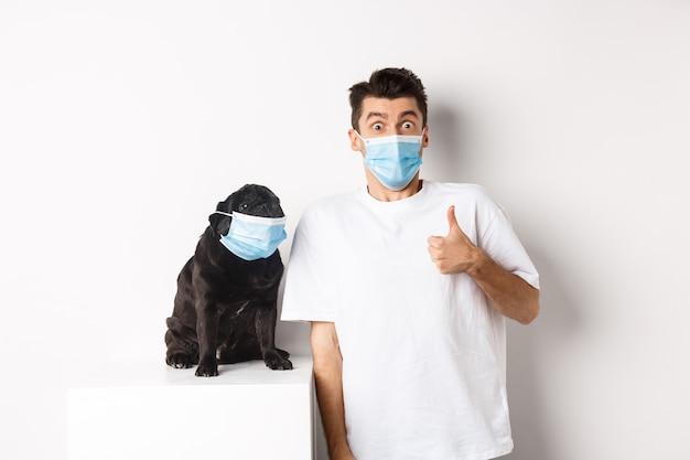 Covid-19, dieren en quarantaineconcept. afbeelding van grappige jongeman en kleine hond met medische maskers, eigenaar die duim omhoog laat zien in goedkeuring of zoals, witte achtergrond.