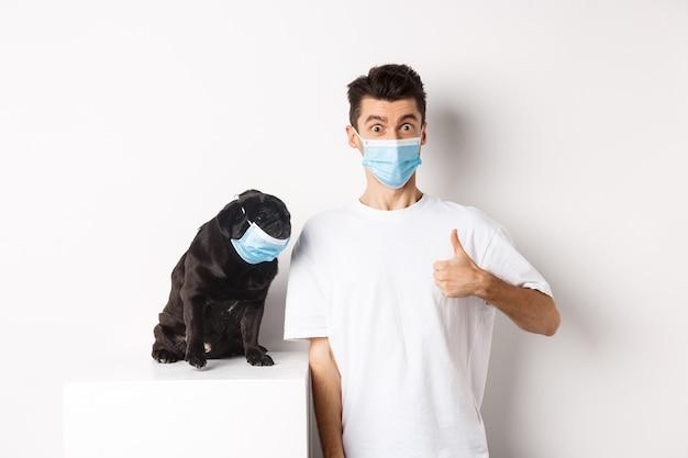 Covid-19, dieren en quarantaineconcept. afbeelding van grappige jongeman en kleine hond met medische maskers, eigenaar die duim omhoog laat zien, prijs iets, witte achtergrond