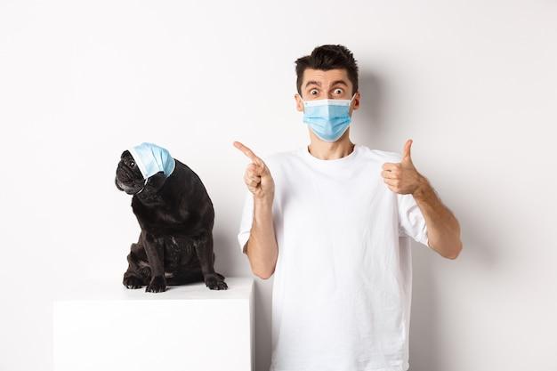 Covid-19, dieren en quarantaineconcept. jonge man en zwarte hond met medische maskers, mopshond die naar de linkerbovenhoek kijkt en eigenaar die duim omhoog laat zien om promo te prijzen.