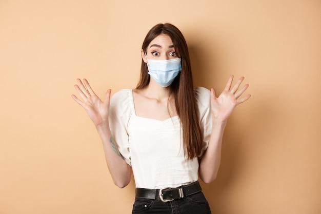 Covid-19 en levensstijlconcept. verraste vrouw in medisch masker schreeuw opgewonden, handen opsteken en groot nieuws schreeuwen, staande op beige achtergrond.