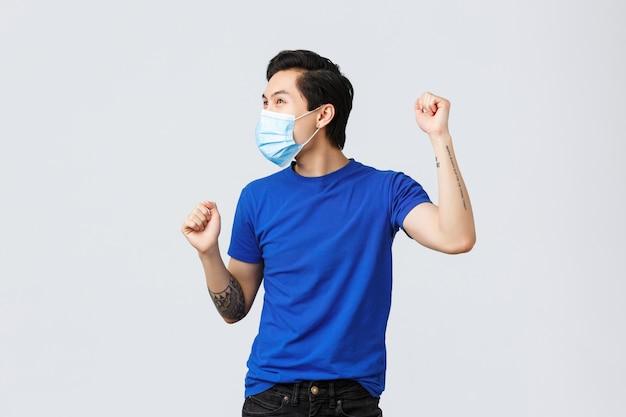Covid-19 en lifestyle concept. verheugd gelukkig jonge aziatische man voelt triomf, handen omhoog en dansen, vieren overwinning of prestatie