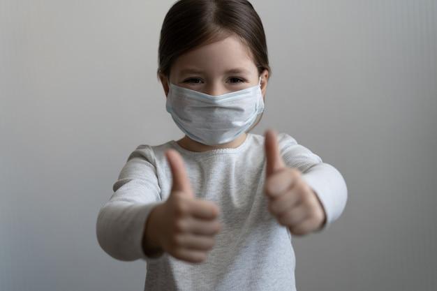 Covid-19 en luchtverontreinigingsconcept. meisje draagt masker ter bescherming en duim omhoog gebaar voor de uitbraak van het coronavirus. coronavirus en epidemische virussymptomen