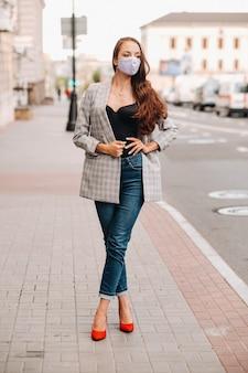 Covid-19 en luchtvervuiling pm2.5 concept. pandemie, portret van een jonge vrouw die een beschermend masker op straat draagt. concept gezondheid en veiligheid.