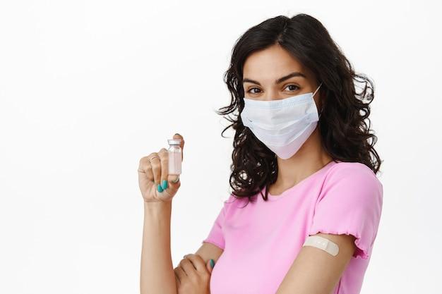Covid-19 en vaccinatieconcept. brunette israili meisje met medisch masker toont ampul met vaccin tegen coronavirus, glimlachend en zelfverzekerd op wit