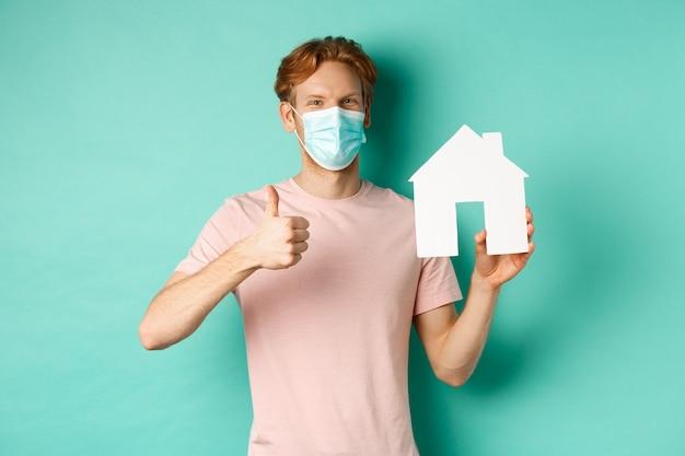 Covid-19 en vastgoedconcept. vrolijke man in gezichtsmasker met huisuitsparing en duim omhoog, staande over turkooizen achtergrond