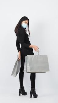 Covid 19 en winkelconcept. aziatische vrouw die de boodschappentas van de gezichtsmasker draagt. meisje en papieren zak staan voor winkelen tijdens de coronaviruscrisis of de uitbraak van covid19. shopper en virusmasker.