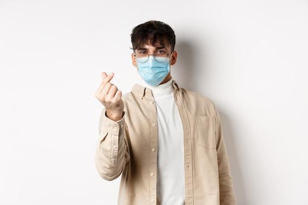 Covid-19, gezondheids- en echte mensenconcept. leuke jonge mens in medisch masker dat vingerhart toont en kijkt, die zich op witte muur bevindt.