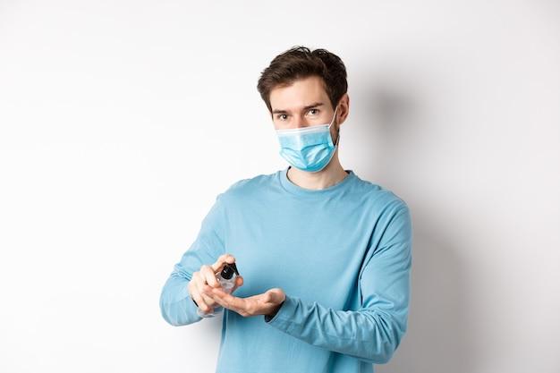 Covid-19, gezondheids- en quarantaineconcept. blanke man in medisch masker met handdesinfecterend middel, antisepticum van coronavirusverspreiding, witte achtergrond toepassen.