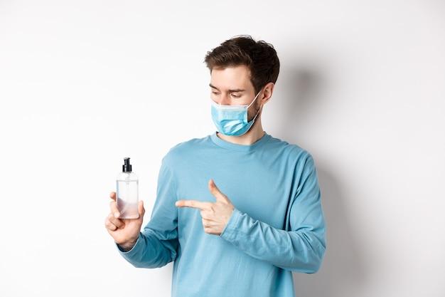 Covid-19, gezondheids- en quarantaineconcept. jonge man wijzend en kijken naar hand sanitizer fles, met goede antiseptische, witte achtergrond.
