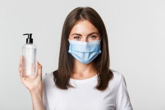 Covid-19, gezondheids- en sociaal afstandsconcept. close-up van aantrekkelijk glimlachend meisje in medisch masker, dat handdesinfecterend middel toont, adviseert antiseptisch.