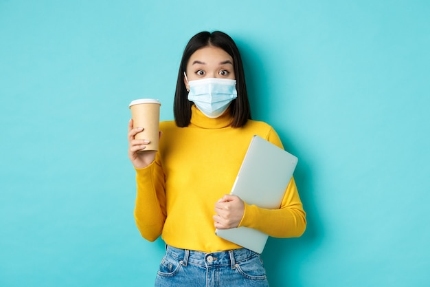 Covid-19, gezondheidszorg en quarantaineconcept. aziatische studente met medisch masker staat met laptop en koffie uit café, staande over blauwe achtergrond