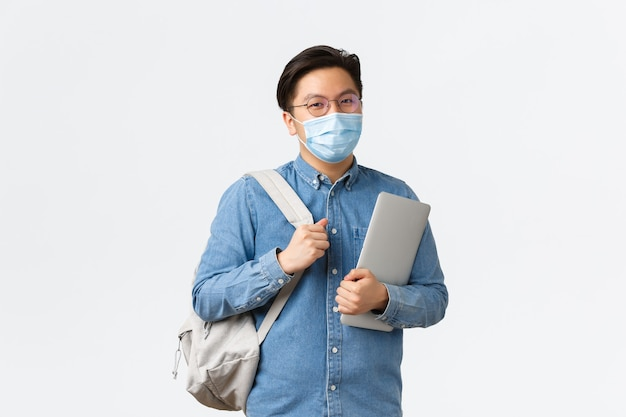 Covid-19, het voorkomen van virussen en sociale afstand bij het universitaire concept. glimlachende aziatische mannelijke student met medisch masker die naar lessen gaat op de universiteit, laptop en rugzak vasthoudt, staande op een witte achtergrond.