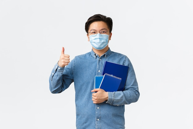 Covid-19, het voorkomen van virussen en sociale afstand bij het universitaire concept. vrolijke aziatische mannelijke leraar of tutor met medisch masker draagt notitieboekjes en studiemateriaal, met duimen omhoog, witte achtergrond.