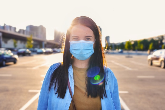 Covid-19-infectie-uitbraakpreventieconcept. coronavirus. portret van een jonge vrouw met wegwerp medisch masker op haar gezicht staande op straat in de stad