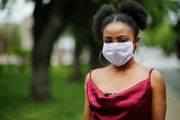 Covid-19, infectieus virus. afrikaanse vrouw met krullend haar, draagt rode zijden jurk en medisch wegwerpmasker, geeft om haar gezondheid en beschermt in gevaarlijke situaties.