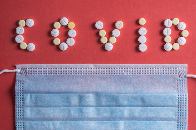 Covid 19-letters gemaakt van witte medische pillen op een felroze achtergrond.