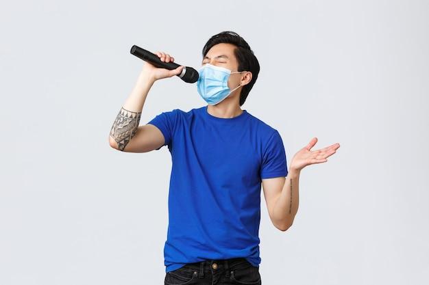 Covid-19 levensstijl, emoties van mensen en vrije tijd op quarantaineconcept. knappe grappige jonge mannelijke student die thuis blijft tijdens de pandemie van het coronavirus, een masker draagt en karaoke in de microfoon zingt.