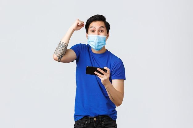 Covid-19 levensstijl, emoties van mensen en vrije tijd op quarantaineconcept. vrolijke vrolijke aziatische man die wint in het spel, het niveau heeft gehaald op mobiele arcade, hand in triomf opsteekt, smartphone vasthoudt.