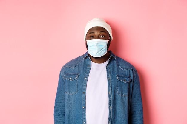 Covid-19, levensstijl en quarantaineconcept. gelukkig zwarte man in muts en gezichtsmasker lachend met ogen, staande op roze achtergrond