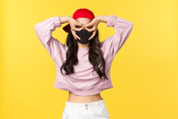 Covid-19, levensstijl op sociale afstand, preventie van virusverspreidingsconcept. grappig en schattig aziatisch meisje met gezichtsmasker en rode dop, maak een nepbril met vingers over de ogen, staar verrast en onder de indruk.