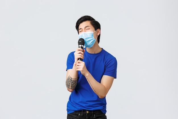 Covid-19 levensstijlconcept. zorgeloos grappige jonge koreaanse man, aziatische man in medische masker met microfoon en karaoke met passie sining