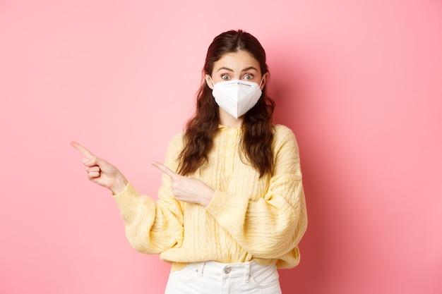 Covid-19, lockdown en pandemie concept. jonge nieuwsgierige vrouw demonstreerde promotietekst, wees met de vingers opzij en droeg een gasmasker voor preventieve maatregelen, roze muur.