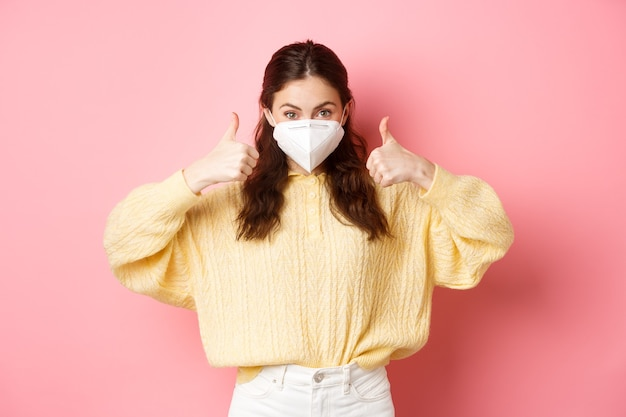 Covid-19, lockdown en pandemie concept. jonge vrouw met gasmasker, gezichtsmasker tijdens quarantaine, duimen opdagen ter goedkeuring, vaccinatie ondersteunen, roze muur.