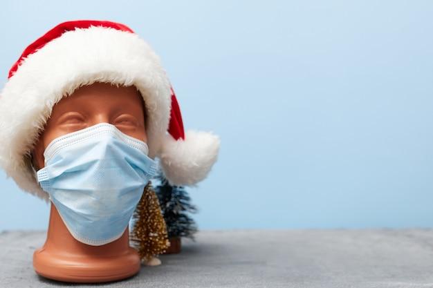 Covid 19, medisch masker op een etalagepop en kerstmuts 2021 op blauwe achtergrond