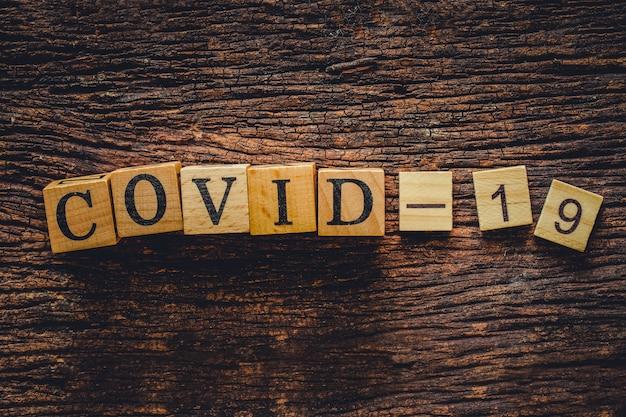 Covid-19-naam van corona-virustekst op oud houtblok voor ontwerp van de achtergrond van de banner van de webtitel.