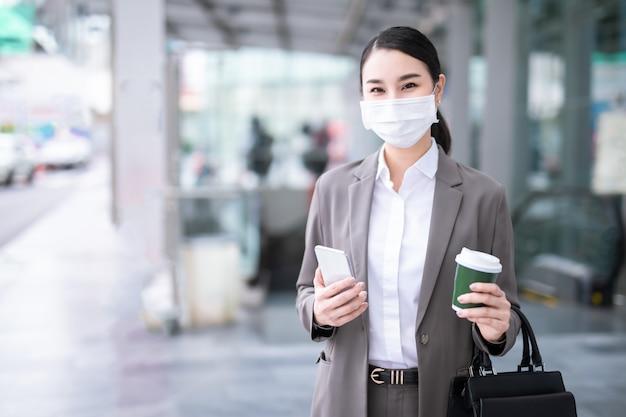 Covid-19 pandemic coronavirus aziatische vrouw in stadsstraat met gezichtsmasker dat beschermt tegen verspreiding van ziektevirus sars-cov-2. meisje met beschermend masker op gezicht tegen de ziekte van coronavirus 2019.