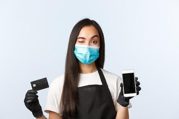 Covid-19 pandemie, coffeeshop, kleine bedrijven en het voorkomen van virusconcept. brutale aantrekkelijke aziatische barista, vrouwelijke cafémedewerker met medisch masker en handschoenen knipoogt, toont creditcard en telefoon