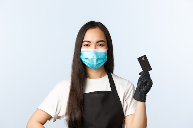 Covid-19 pandemie, coffeeshop, kleine bedrijven en het voorkomen van virusconcept. glimlachende schattige aziatische vrouwelijke barista, serveersteradvies gebruik contactloze betaalmethode, houd creditcard vast