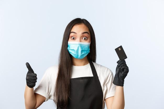 Covid-19 pandemie, coffeeshop, kleine bedrijven en het voorkomen van virusconcept. opgewonden aantrekkelijke aziatische vrouwelijke barista, winkelmedewerker laat duim omhoog zien als uitleg over creditcardprofs