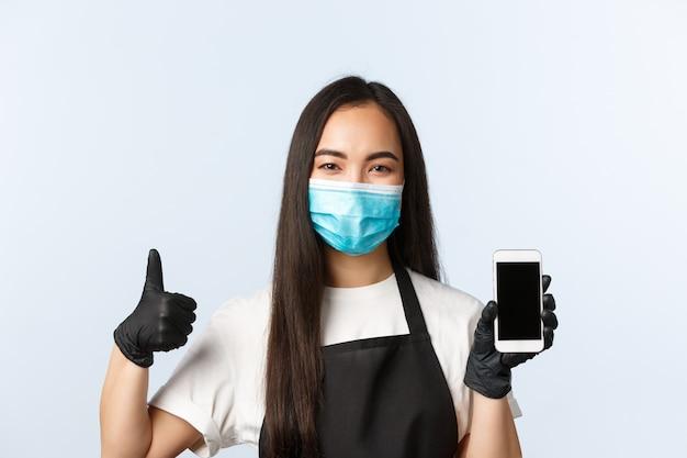 Covid-19 pandemie, coffeeshop, kleine onderneming en het voorkomen van virusconcept. de glimlachende aantrekkelijke aziatische koffieeigenaar, barista die het smartphonescherm tonen en duim-omhoog, dragen medisch masker