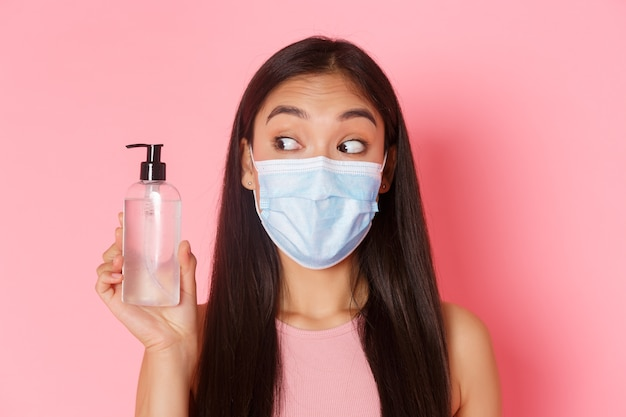 Covid-19 pandemie, coronavirus en sociaal distantiëren concept. close-up van schattig en dwaas, mooi aziatisch meisje in medisch masker kijken naar handdesinfecterend middel, advies met behulp van antiseptica, roze muur